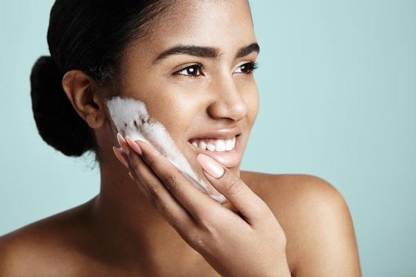 kobieta myje twarz. Jak rozświetlić twarz?